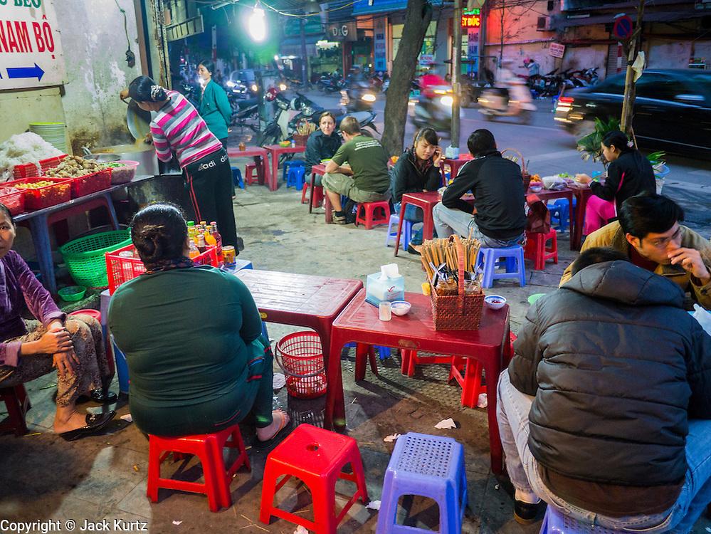 31 MARCH 2012 - HANOI, VIETNAM:   People at street side food stalls in the Old Quarter of Hanoi, Vietnam.    PHOTO BY JACK KURTZ