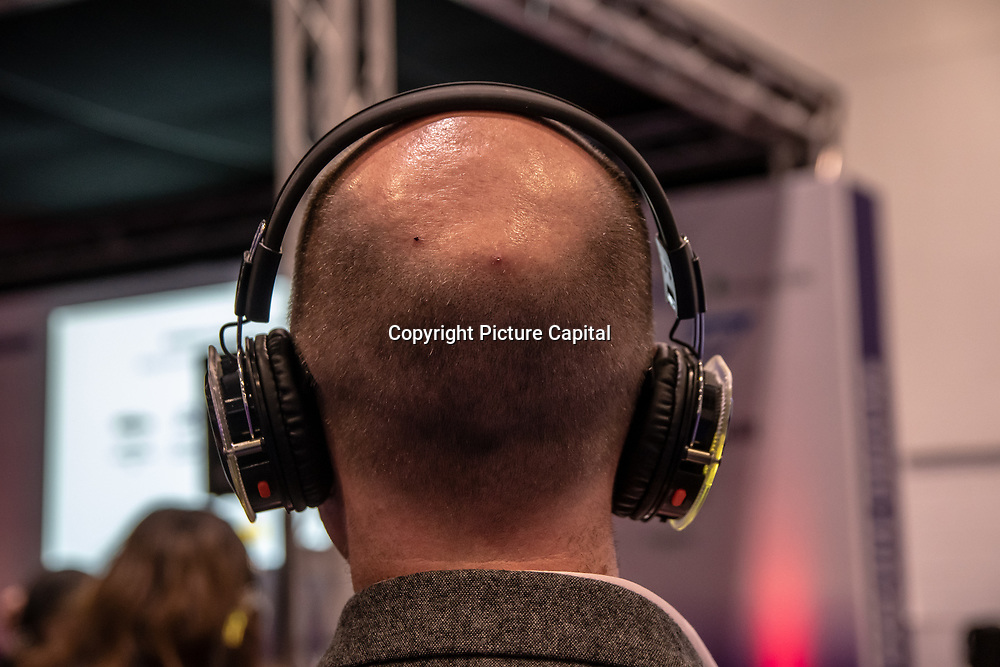 People wearing headphone to listen to a speaker at London Tech Week at Excel London,on 12 June 2019, UK