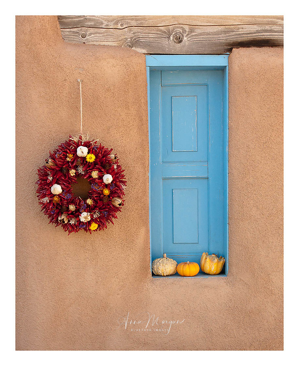 Thanksgiving decorations on an adobe building with blue painted window, chilli wreath and pumpkins