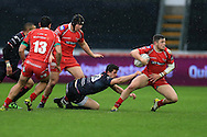 Steffan Evans of the Scarlets ® breaks away from the tackle from Owen Watkin of the Ospreys. Guinness Pro12 rugby match, Ospreys v Scarlets at the Liberty Stadium in Swansea, South Wales on Saturday 26th March 2016.<br /> pic by  Andrew Orchard, Andrew Orchard sports photography.
