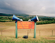 An old fashioned pair of public address speakers have been attached to a no access sign overlooking the Northumberland countryside at the Kielder Air Show. Here, the elite 'Red Arrows', Britain's prestigious Royal Air Force aerobatic team, are to perform and the squadron's commentator - known as Red 10 - will be describing the 25-minute routine performed in front of a few hundred people, probably the smallest of the Red Arrows audiences. The Hawk aircraft will be flying over the borderland between England and Scotland during this display which has attracted a local crowd to this pretty landscape. This primitive method of amplification makes for it charmingly quirky. Tangled electrical wires and an extension reel is low-tech and makeshift, vastly different to other shows where digital sound quality reproduces audio to many of thousands of spectators.