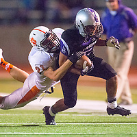092013       Brian Leddy<br /> Miyamura Patriot Adner Palma (5) is tackled by Aztec Tiger  Jake Harris (21) during a game on Sept. 20.