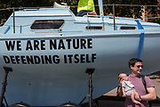 A man stands with a young child next to a climate change boat opposite the Old Vic in Waterloo during the week-long, country-wide protest by environmental campaigners, Extinction Rebellion, on 16th July 2019, in London, England. The five-day summer uprisings message is for the UK government to outlaw what protesters call Ecocide.