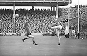 Kerry defender shoots the ball past a Down forward during the All Ireland Senior Gaelic Football Final Kerry v Down in Croke Park on the 22nd September 1968. Down 2-12 Kerry 1-13. Lensmen photographer focused on net as it looked like Down were to add another score!