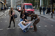 While crossing the road with a Royal Mail Parcelforce van in the road of the capitals financial district, a UPS courier is helped by a lady to pick up dropped parcels, on 5th October, 2017, in the City of London, England.