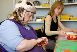 Day Service Officer working alongside service user who taking part in a hand painting activity,
