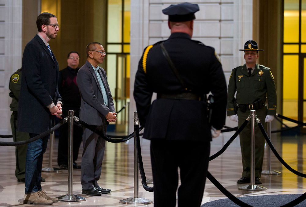 From left: State Sen. Scott Wiener and Board of Supervisors Norman Yee pay their respect as San Francisco Mayor Ed Lee lies in state at City Hall on Friday, Dec. 15, 2017, in San Francisco, Calif. Lee died on Tuesday from a heart attack. He was 65 years old.