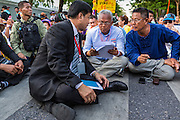 12 MAY 2014 - BANGKOK, THAILAND: SUTHEP THAUGSUBAN (center, blue shirt) meets with representatives of the Thai Senate while they sit in Phichai Road near the Parliament building in Bangkok. Several thousand protestors with the People's Democratic Reform Committee (PDRC) blocked access to the Thai Parliament building in Bangkok as a part of their continuing anti-government protests. The Parliament is not currently in session and was dissolved by former Prime Minister Yingluck Shinawatra but the Senate is in session. The protestors are demanding that the Senate dissolve the current Pheu Thai caretaker government and appoint a new Prime Minister and cabinet. Members of the Senate leadership met with Suthep Thaugsuban Monday to discuss the impasse.   PHOTO BY JACK KURTZ