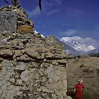 HIMALAYA, NEPAL. 3- year old Ben Wiltsie romps by Tibetan Buddhist chorten, Khumjung village, Khumbu region. Mts. Everest & Lhotse bkg.
