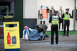 © Licensed to London News Pictures . 24/10/2018. Leeds , UK . Three people huddled together on the pavement on Briggate are moved on by PCSOs in Leeds City Centre . At least six people sleeping rough have died in the Metropolitan Borough of the City of Leeds since March 2017 and West Yorkshire Police say they responded to 66 reported cases of people suffering the effects of Spice in July 2018 , a large increase on previous months . Photo credit : Joel Goodman/LNP