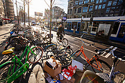 In Amsterdam fietst een man op het Rokin langs een rij slordig geparkeerde fietsen.<br /> <br /> In Amsterdam a man on a bicycle passes parked bikes at the Rokin.