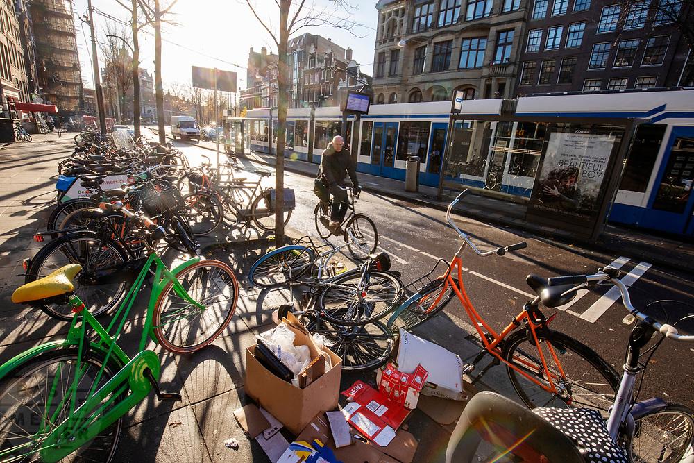 In Amsterdam fietst een man op het Rokin langs een rij slordig geparkeerde fietsen.<br /> <br /> In Amsterdam a man on a bicycle passes parked bikes at the Rokin.