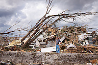 A man stands in front of a home he crawled out of after a tornado in Joplin, Missouri, May 25, 2011.  On May 22, 2011, Joplin Missouri was devastated by an EF-5 tornado.