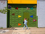 A young woman with fiery red hair compliments the colorful entrance to courtyard apartments in the Fishtown neighborhood of Philadelphia