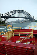 Top-deck seating on Sydney Harbour Ferry, with Sydney Harbour Bridge in background. Sydney, Australia