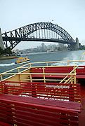 Top-deck seating on Sydney Harbour Ferry, with Sydney Harbour Bridge in background. Sydney, Australia
