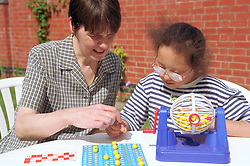 Mother and girl with downs syndrome playing a game together,