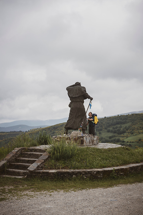Francois, from Canada and walking the Camino with his family, touches the famous pilgrim statue on Alto de San Roque.  (July 4, 2018)