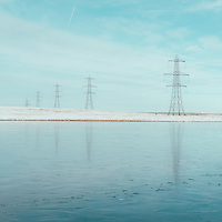 Electric pylons and reservoir with snow in Yorkshire