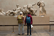 Visitors admire the sculpture of the ancient Greek Parthenons Elgin Marbles Metopes in the British Museum, on 11th April 2018, in London, England.