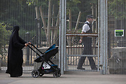 A Muslim lady walks past UK Met police officers who guard a temporary perimeter fence encircling Winfield House, the official residence of the US Ambassador during the visit to the UK of US President, Donald Trump, on 12th July 2018, in Regent's Park, London, England.