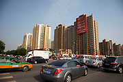 Cars streaming past a housing development in southeast Beijing, China. Once a city of bicycles, Beijing is now a car city with traffic jams and a road system full to capacity. In addition to this, it is also a city growing into the sky as blocks of apartment buildings are being constantly built.