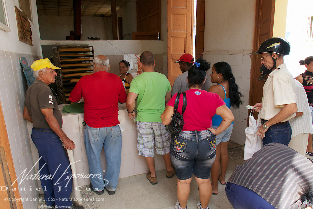 People waiting in line for fresh bread at one of many Food Ration stores in Trinidad, Cuba.