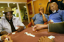 Elderly people play dominoes at a multi-cultural  day centre; Bradford