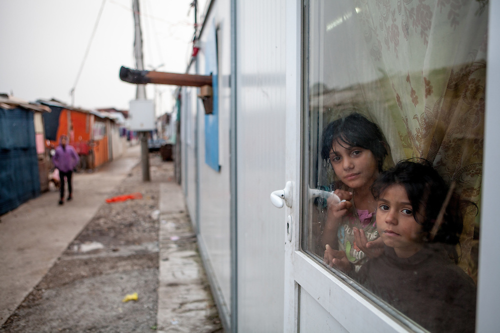 Two girls living at Konik Camp located in the suburbs of the city of Podgorica, Montenegro. A huge fire in 2012 detroyed a big part of the refugee camp and many of the inhabitants are living in containers. The housing pictured belongs to the part with new housing facilities.