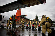 "A crew of veteran jumpers practice ""Hit It"" drills with training foreman Larry Wilson before boarding a Twin Otter plane for live proficiency jumps."