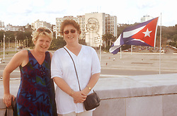 Two women standing in Revolution Square; Havana; Cuba; in front of the Ministry of the Interior building which has a picture of Che Guevara painted on its side,