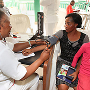 INDIVIDUAL(S) PHOTOGRAPHED: From left to right: Siyanbade Mojisola, Jenifer, and unknown. LOCATION: Onigbongbo Health Care Center, Lagos, Nigeria. CAPTION: Siyanbade Mojisola takes a patient's blood pressure, accompanied by her 10-year-old daughter, who boosts their mood.