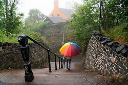 Woman with colourful umbrella descends steps at Calton Hill on rainy day, Edinburgh, Scotland, UK