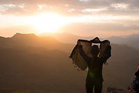 Iran, Dizin, 12.08.2016: Eine junge iranische Frau löst ihren Schal, nahe Dizin, abendlicher Blick auf das Alborz-Gebirge.