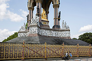 A child pushes a buggy in front of the golden ironwork at the Albert Memorial in Kensington Park, on 20th August 2019, in London, England. The Albert Memorial, directly north of the Royal Albert Hall in Kensington Gardens, London, was commissioned by Queen Victoria in memory of her beloved husband Prince Albert, who died in 1861. Designed by Sir George Gilbert Scott in the Gothic Revival style, it takes the form of an ornate canopy or pavilion 176 feet tall, in the style of a Gothic ciborium over the high altar of a church, sheltering a statue of the prince facing south. It took over ten years to complete, the £120,000 cost met by public subscription.