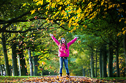 © Licensed to London News Pictures. 25/10/2015. Leeds, UK. Ten year old Cerys throws leaves into the air at Temple Newsam Park in Leeds on a crisp sunny Autumn morning. Photo credit: Andrew McCaren/LNP