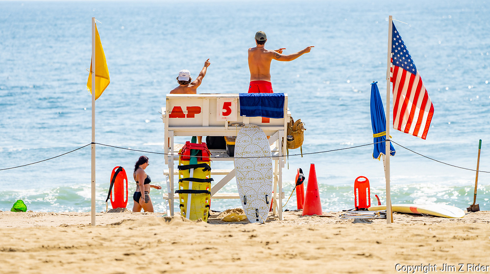 Lifeguards on the beach in Asbury Park direct swimmers back into the swimming area.