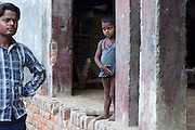 A young boy (right) and a man (left) and facing each other on a road inside Rajbhar village, where Neelam Bharadwaj, 16, (name changed) resides with her family, around 20 kilometres away from Varanasi, in Uttar Pradesh, India. Neelam was raped when she was 13 years old. After walking to a local shop on the main road neighbouring her village, she was forcibly picked up by two men. While one of them was raping her in the bushes, the other watched out. After some time, she managed to free herself and run away, hiding under a bridge in cold dirty water for several hours. When she returned home in the morning, the family was too afraid to go to the police, but activist Mangla Parsad, 34, from PVCHR, convinced the family to take the right action. The police initially insulted and threatened the family for bringing the facts up, but filed the official case (FIR) nevertheless. The rape was not mentioned in the file due to an inaccurate and superficial medical record that did not, in fact, mention it. Because of social shame facing by victims of rape in India, the family agreed to wed Neelam to an older man, with help of an agent. After the marriage, her husband raped her again for a whole month before she decided to return home with her family. Neelam's father works in the metal industry in Mumbai and manages to send around 2-3000 INR every month. He only visits the family once in a year. Neelam goes to school and she is studying in 11th Class Standard. She is interested in doing BA in Arts after completing her high school 12th final year.