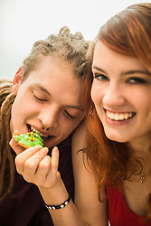 Young woman feeding cookie to her friend, Munich, Bavaria, Germany