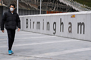 As numbers of Covid-19 cases in Birmingham have increased dramatically in recent weeks, and with the expectation that the city will be added to the watch list of critical areas which may face a local lockdown, people wearing face masks pass near the sign for Birmingham New Street / Grand Central station as they continue to come to the city centre for work and shopping on 18th August 2020 in London, United Kingdom. With other areas in the Midlands under localised lockdown, people and businesses are being urged to follow the Coronavirus advice for workplace and family life help reduce the risk.