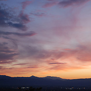 With the mountains in the distance and thin clouds in the sky, the setting Sun creates a dazzling array of purples and oranges in the sky.