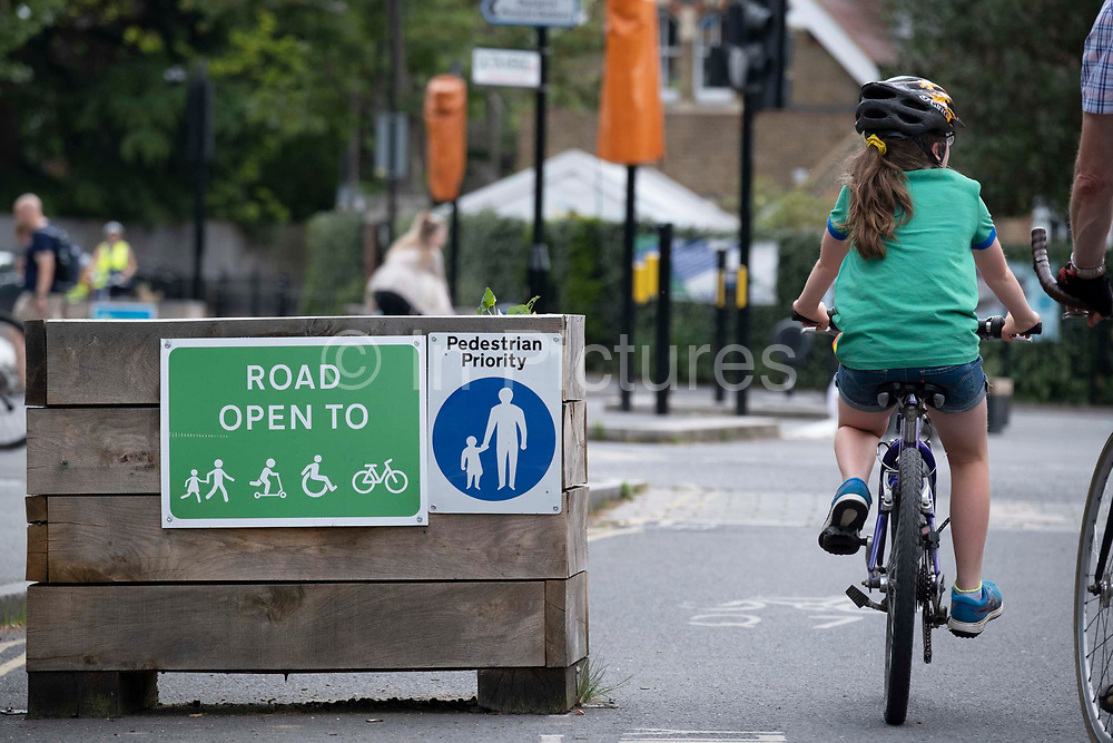 A young cyclist passes through the barriers that form an LTN Low Traffic Neighbourhood, an experimental closure by Southwark Council preventing motorists from accessing the junction of Carlton Avenue and Dulwich Village. Restrictions also prevent traffic from passing through at morning and afternoon rush-hour times in the borough of Southwark, on 14th June 2021, in London, England.