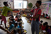 Lunchtime at the Agripada Centre in Mumbai. The older children serve lunch to the younger children. The centre is 1 of 70 centres in India run by the Mumbai Mobile Crèche organisation.