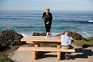 A woman gets ready to perform stretches on a park bench in La Jolla, California.