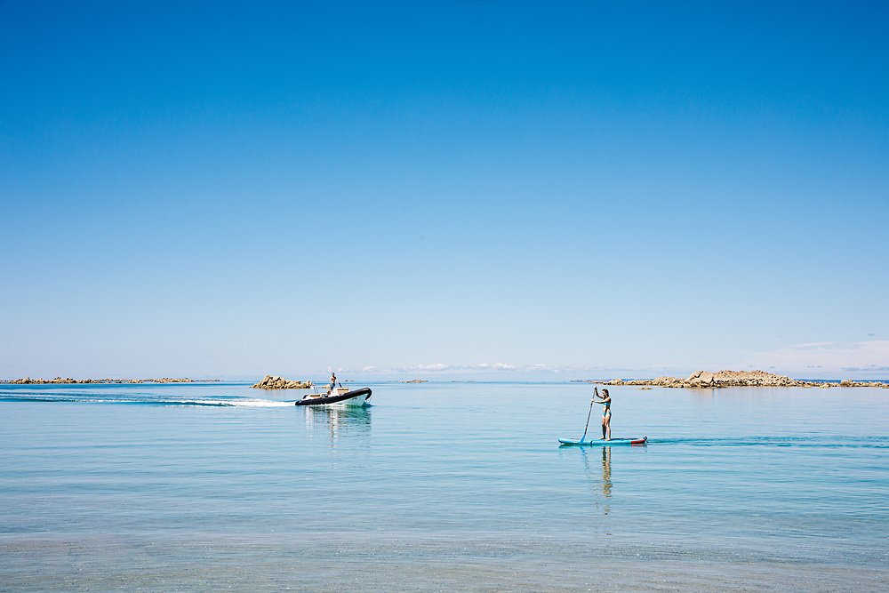 Boat approaching as a lady paddle boards through the calm clear water at the Minquiers sandbanks, off the coast of Jersey CI in summer
