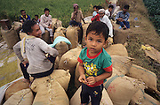 PEASANT FARMING, Malaysia. Peasants farmers  and child sitting  on rice sacks, Kedah state. World Bank funded  project. Poor farmers, peasants, planting, harvesting, cultivating rice padi.