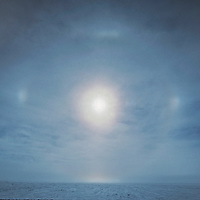 A solar parhelion (sun dog) hovers over sastrugi snow near the South Pole, Antarctica.