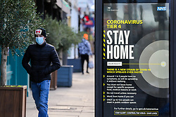 © Licensed to London News Pictures. 02/01/2021. London, UK. A man wearing a protective face covering in north London walks past the government's 'Coronavirus Tier 4 - Stay Home' publicity campaign poster, after the mutated variant of the SARS-Cov-2 virus continues to spread around the country. The President of the Royal College of Physicians, Professor Andrew Goddard, has warned that COVID-19 infection cases are set to rise in the coming weeks and that NHS staff and healthcare workers are worried about the challenges against the virus over the coming months. Photo credit: Dinendra Haria/LNP