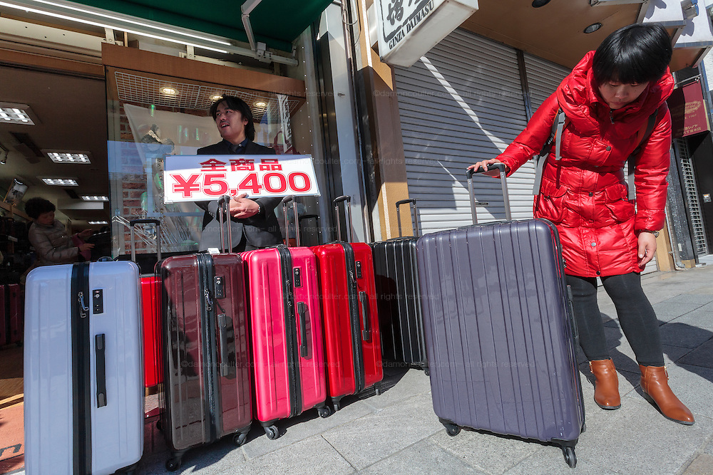 A Chinese tourists looks at cheap suitcases in a store in Ginza, Tokyo, Japan Sunday January 18th 2015. Many Chinese tourists buy additional suitcases to transport their shopping home after visiting Japan which is seeing increasing numbers of tourists arrive, especially from newly affluent China.