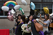 Friends and family of Hillary Chung,, a 21 year-old Law graduate from Hong Kong, celebrate her graduation with a 2:1 degree outside the London School of Economics LSE after her graduation ceremony, on 22nd July 2019, in London, England.